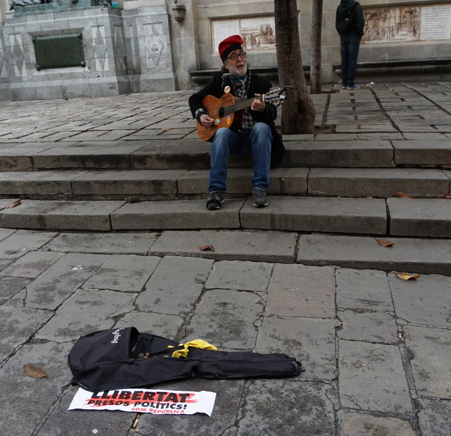 In the Gothic Quarter, a man in a traditional Catalan hat called a  barretina  plays his guitar and sings in support of political prisoners.