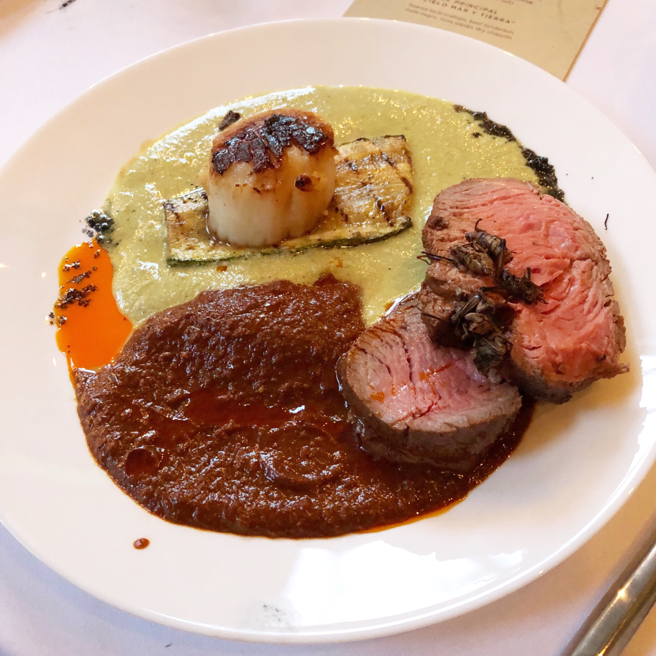 Seared scallops, mole, chapulines, and beef tenderloin by Chef Carlos Raba