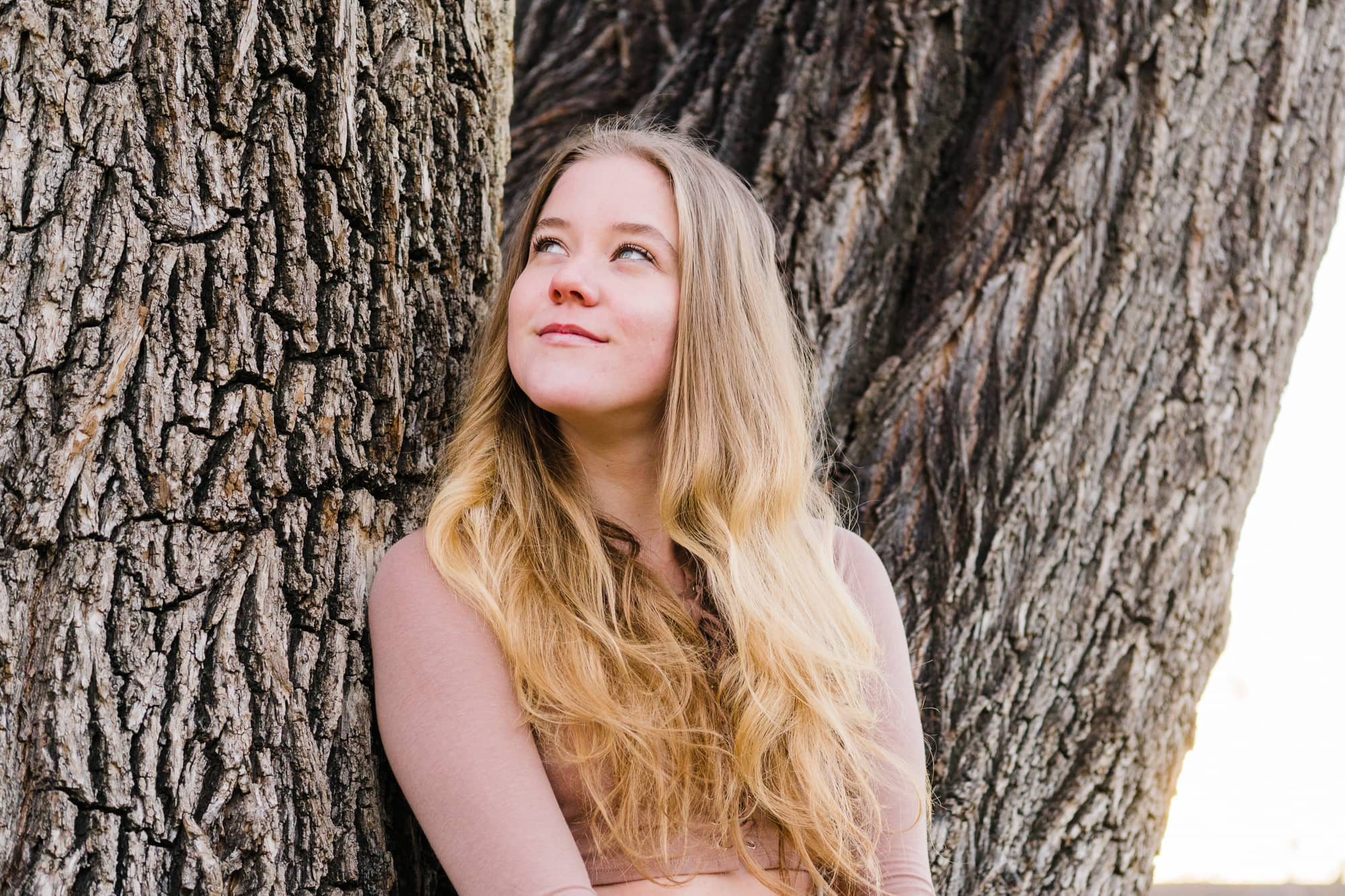 Portrait of woman leaning against tree and looking up in a playfully thoughtful way.