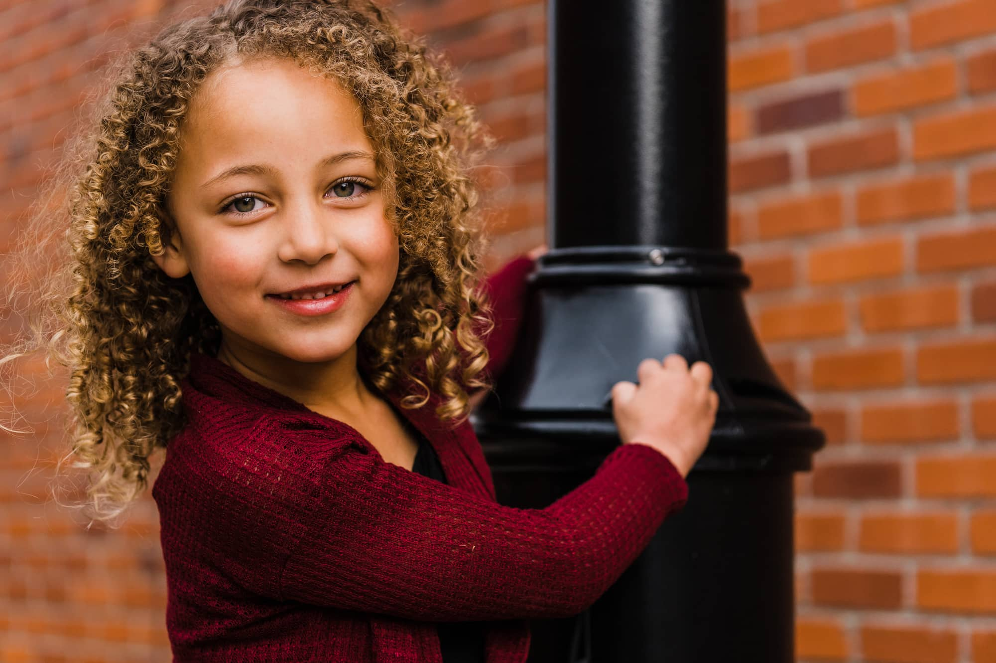 Portrait of young woman hanging from a lamp post.