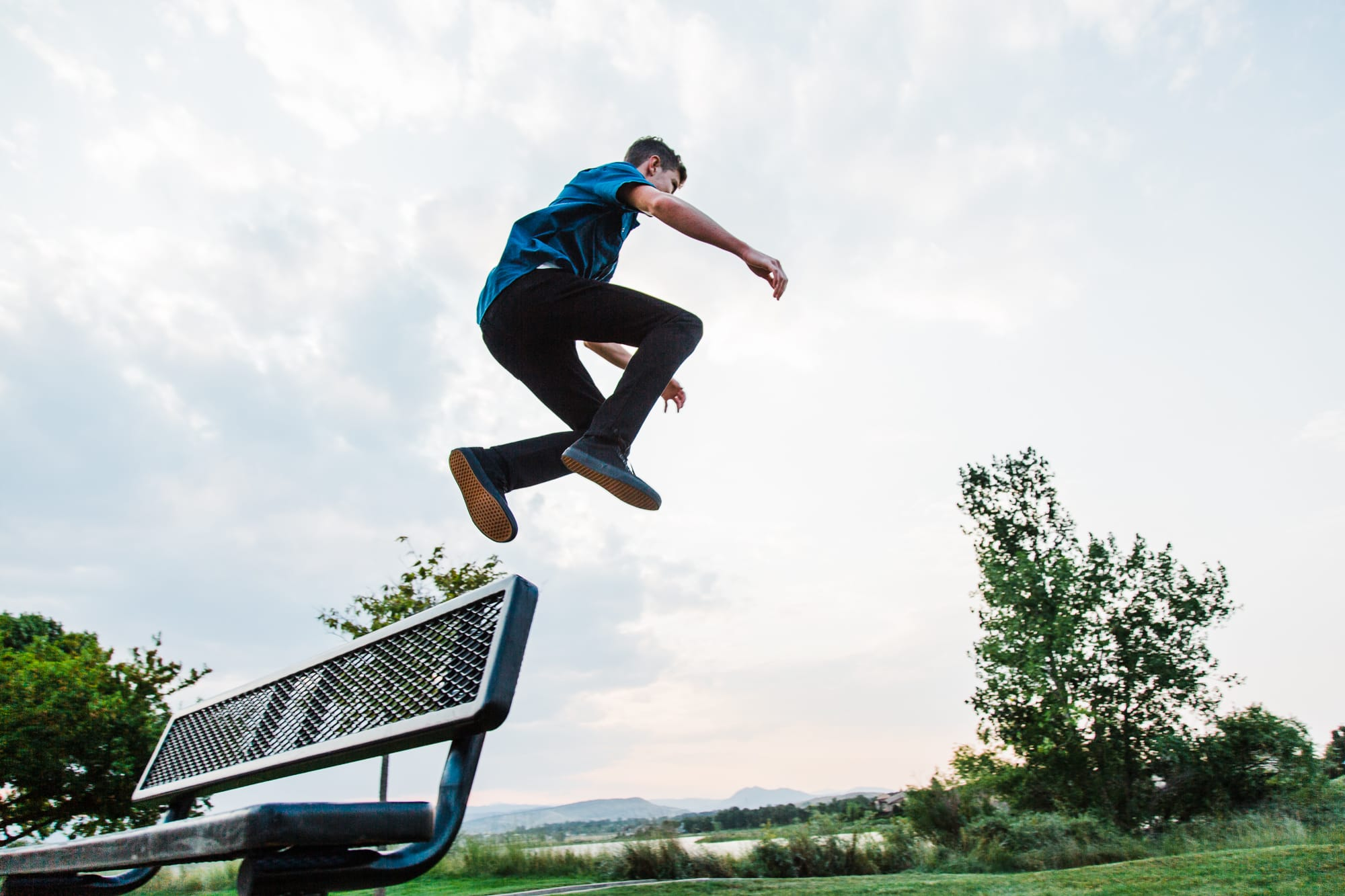 Wide shot of a high school senior guy jumping off the back of a bench.