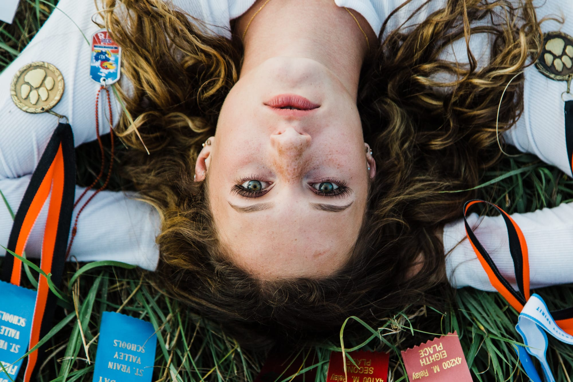 Close up shot of high school senior girl laying in grass surrounded by her ribbons and medals.