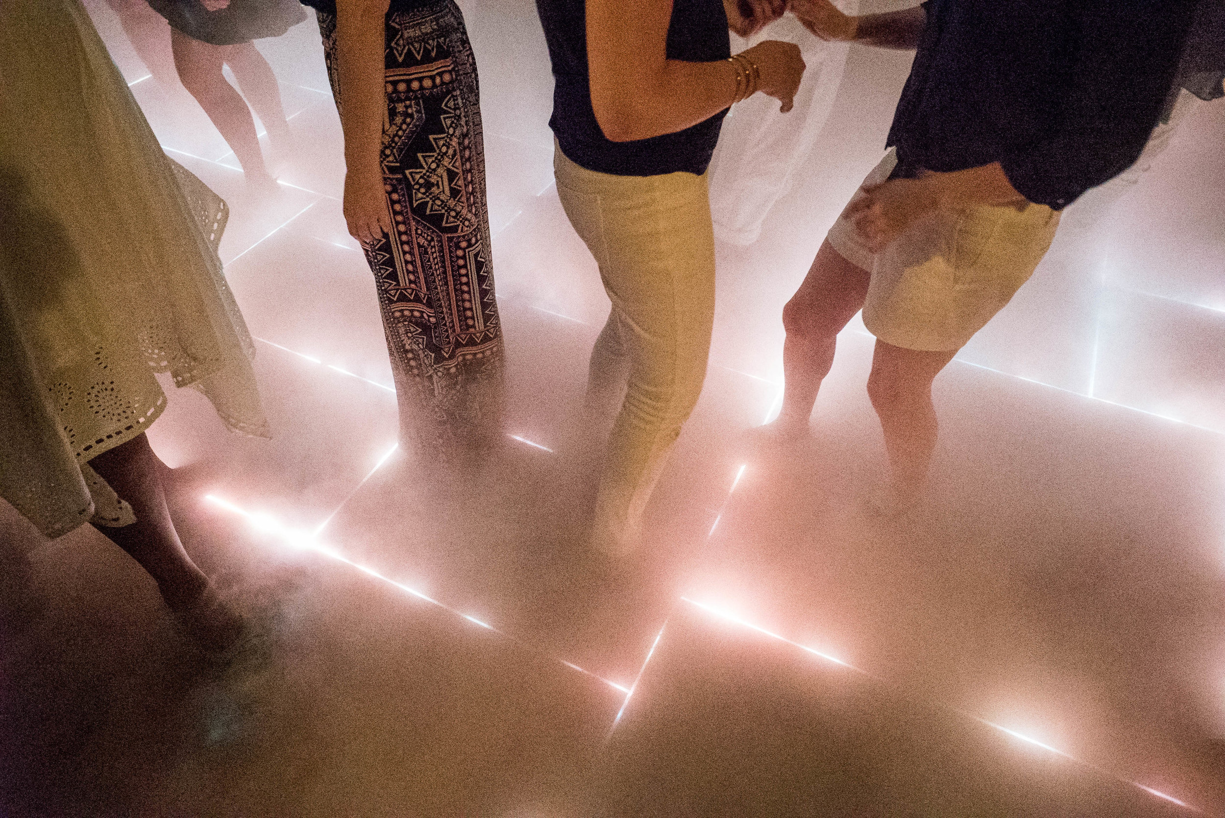 An illuminated dance floor is revealed under low-lying fog. The layout of the light channels was created as a nod to the shape of the shipping channels of the New York harbor.