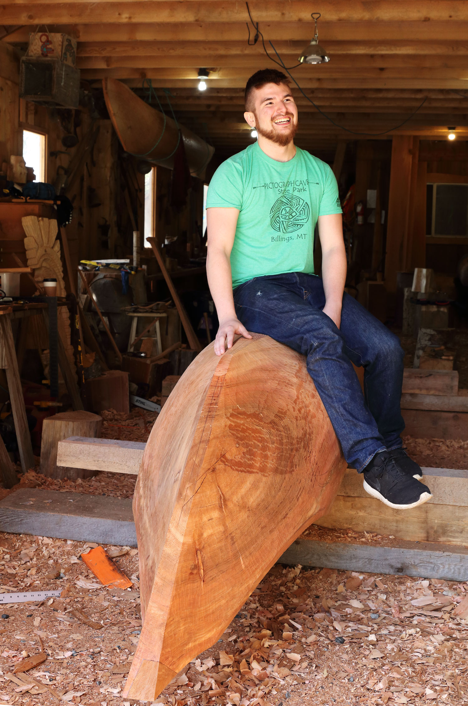 Story Teller and Carver Harley Holter on the canoe that he is carving