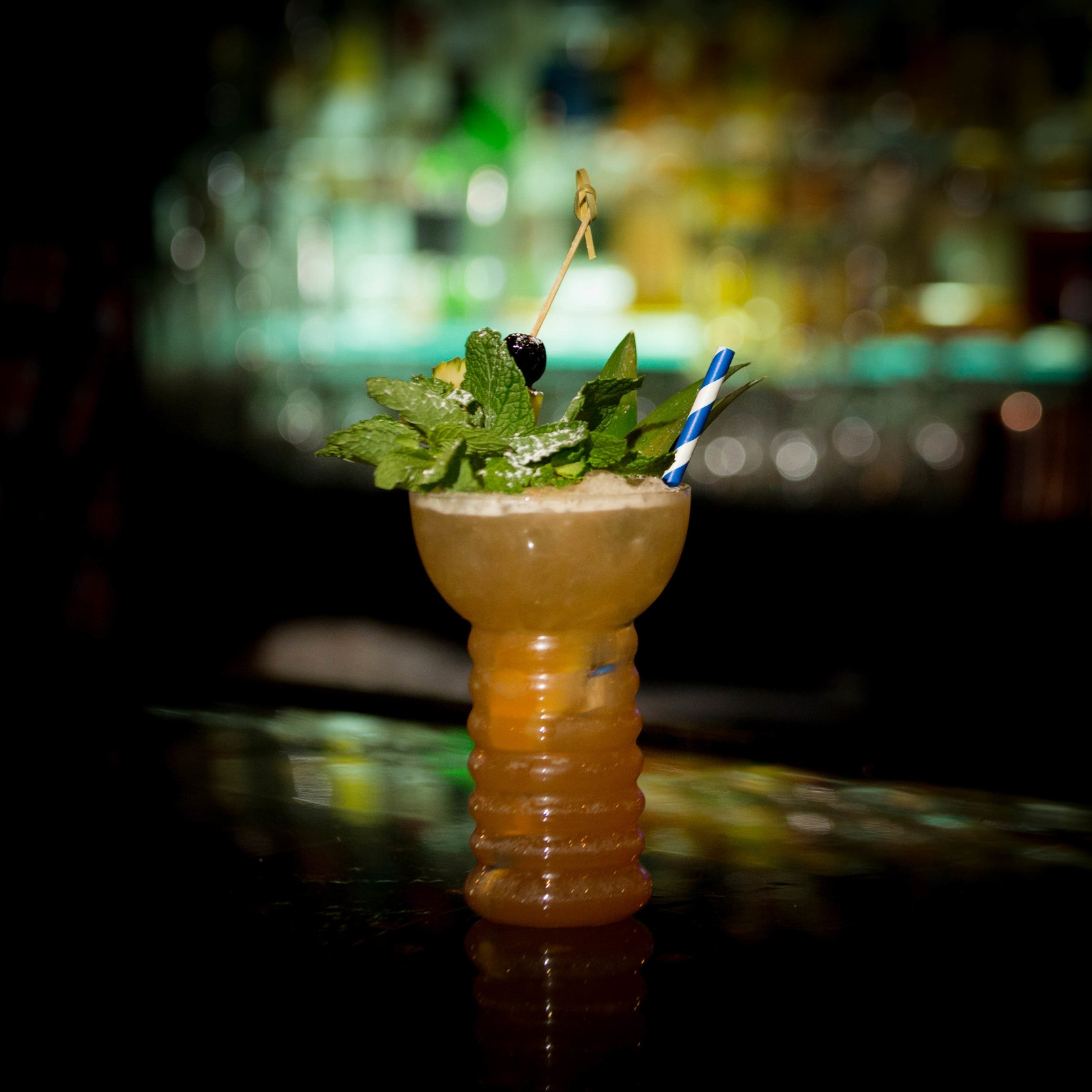OSCEOLA PUNCH   • 1 oz. Hamilton Black • 1 oz. Flor de Cana 7 year • .5 oz. Goslings 151 • 1.5 oz. yaupon tea • 1 oz. lemon juice • .75 oz. honey • .25 oz. Falernum • 3 dashes Herbsaint • 3 dashes Angostura Bitters  • 1. Add all ingredients to drink mixer tin and blend for 5 seconds. • 2. Open pour into a pearl diver glass. • 3. Garnish with a cherry skewered through a pineapple chunk and a mint sprig.