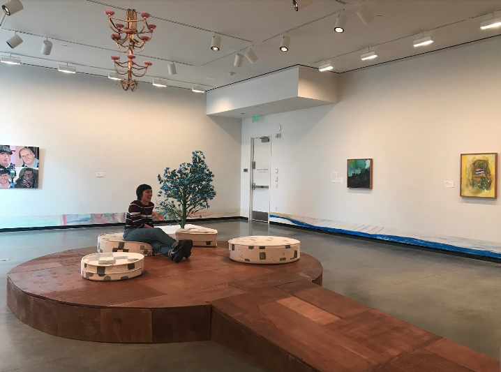 """A view of the stage constructed by Johanson and Jackson being tested by Lily Wilson, a friend of the author's. Lawrence Oliver's """"A Flower Tree"""", 2013, constructed of paper, paint, packing tape, bamboo, and hot glue, also seen."""
