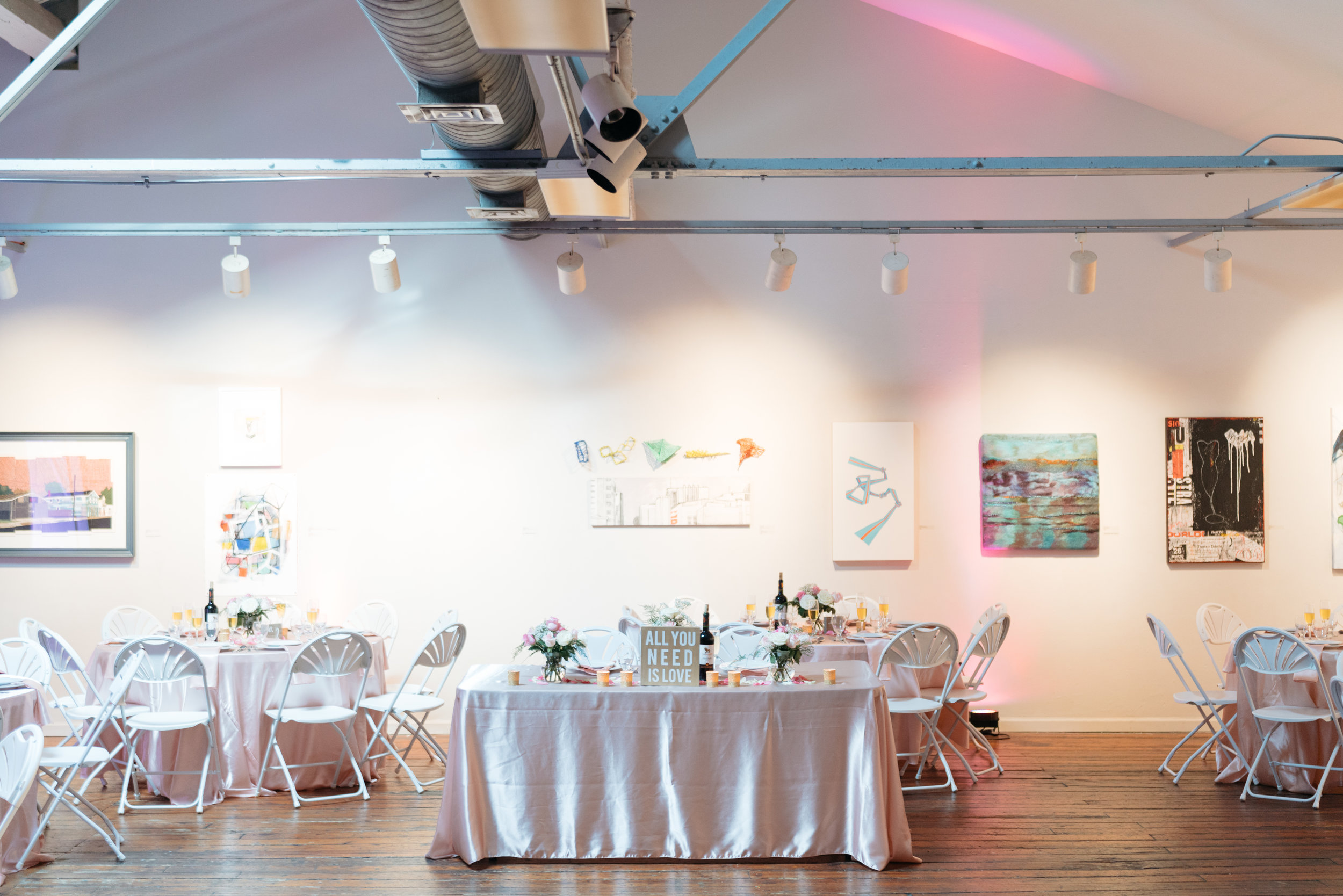 The only obstacle for us with this venue as a whole was making sure the artwork was family friendly- which several pieces were not- thanks to my mom and wedding planner, Jessica Hubacher- they were taken down- hence the empty space.  Bryan and I ended up opting for a sweetheart table and opted to use what the venue provided: a 6 ft. rectangular table. It may seem big and in retrospect it was fantastic. My mom decorated it with flower arrangements she created, one of the vases on the table was very special to me as it was a gift from my mother in law, and a few gold votives, and of course a bottle of amazing chilean wine. The  Chilean wine  was a huge hit, my mom purchased it very inexpensively at her local Trader Joe's.