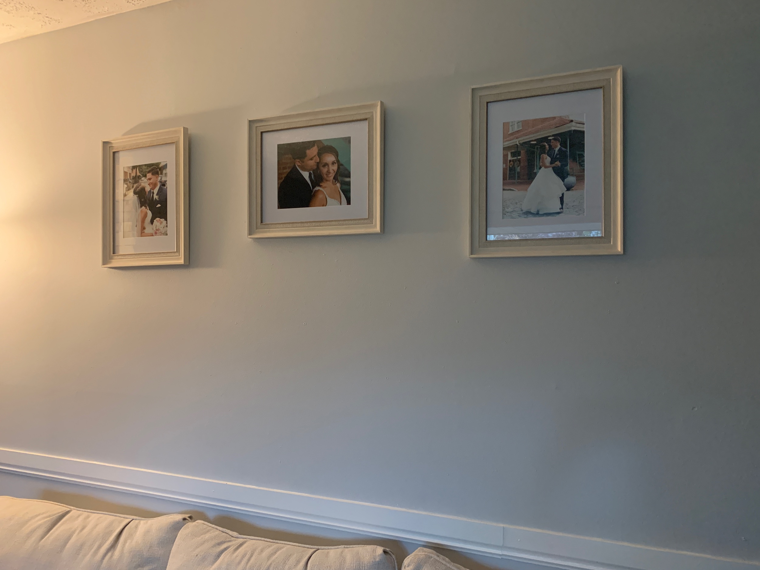 The angle makes it seem like they're not evenly spaced out, but they are! I love these frames because they're subtle and match our beige couch.