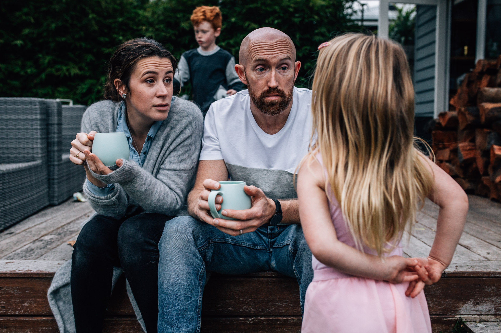 Parents with cups of tea chatting with small daughter.