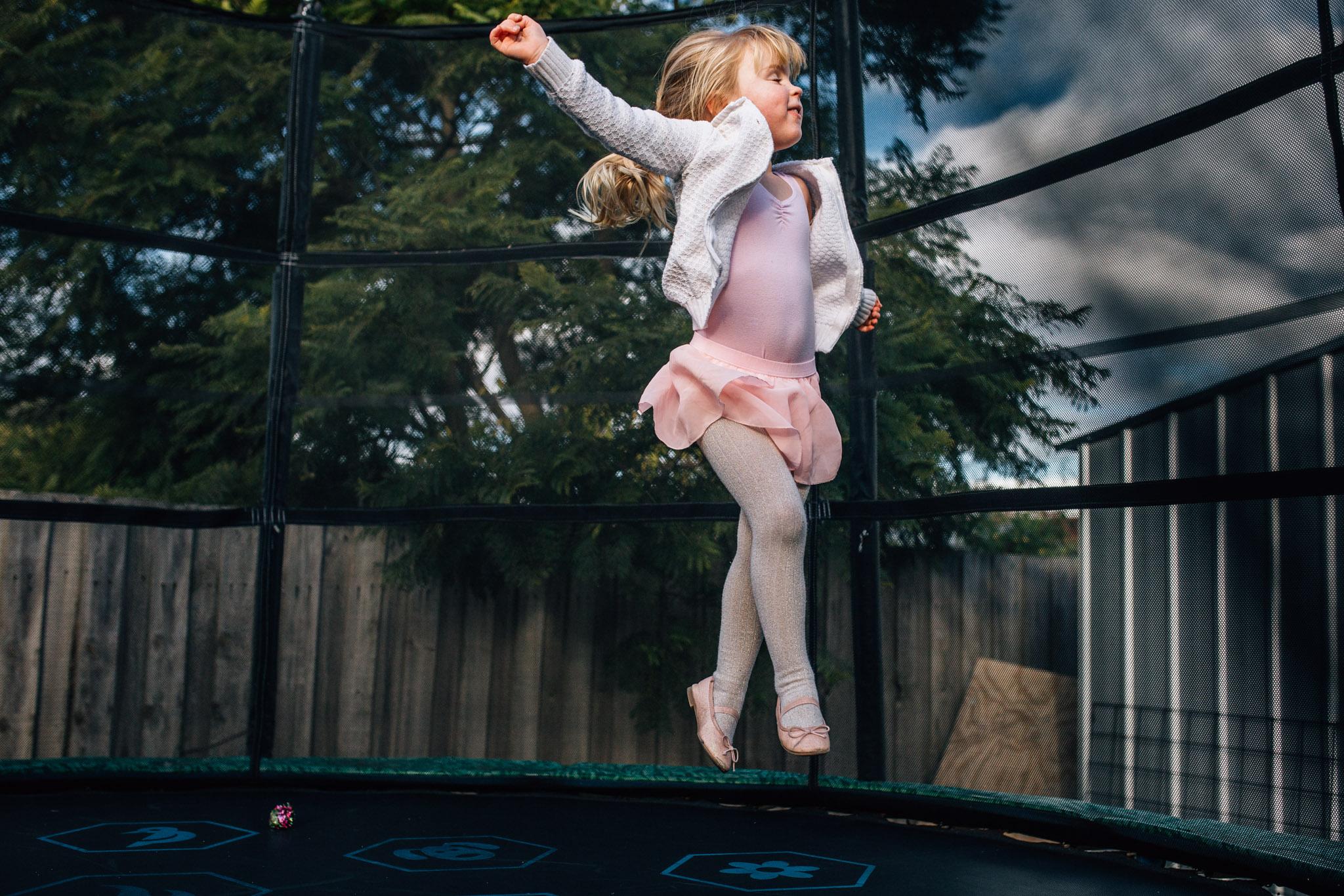 Ballerina girl on trampoline.