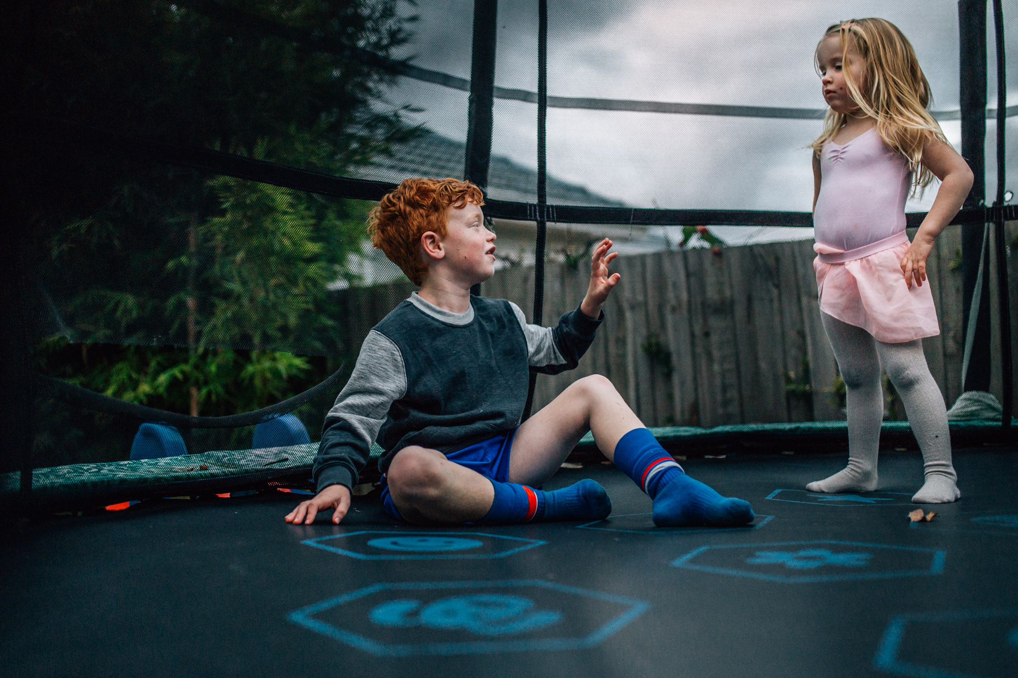 Girl and boy on trampoline.