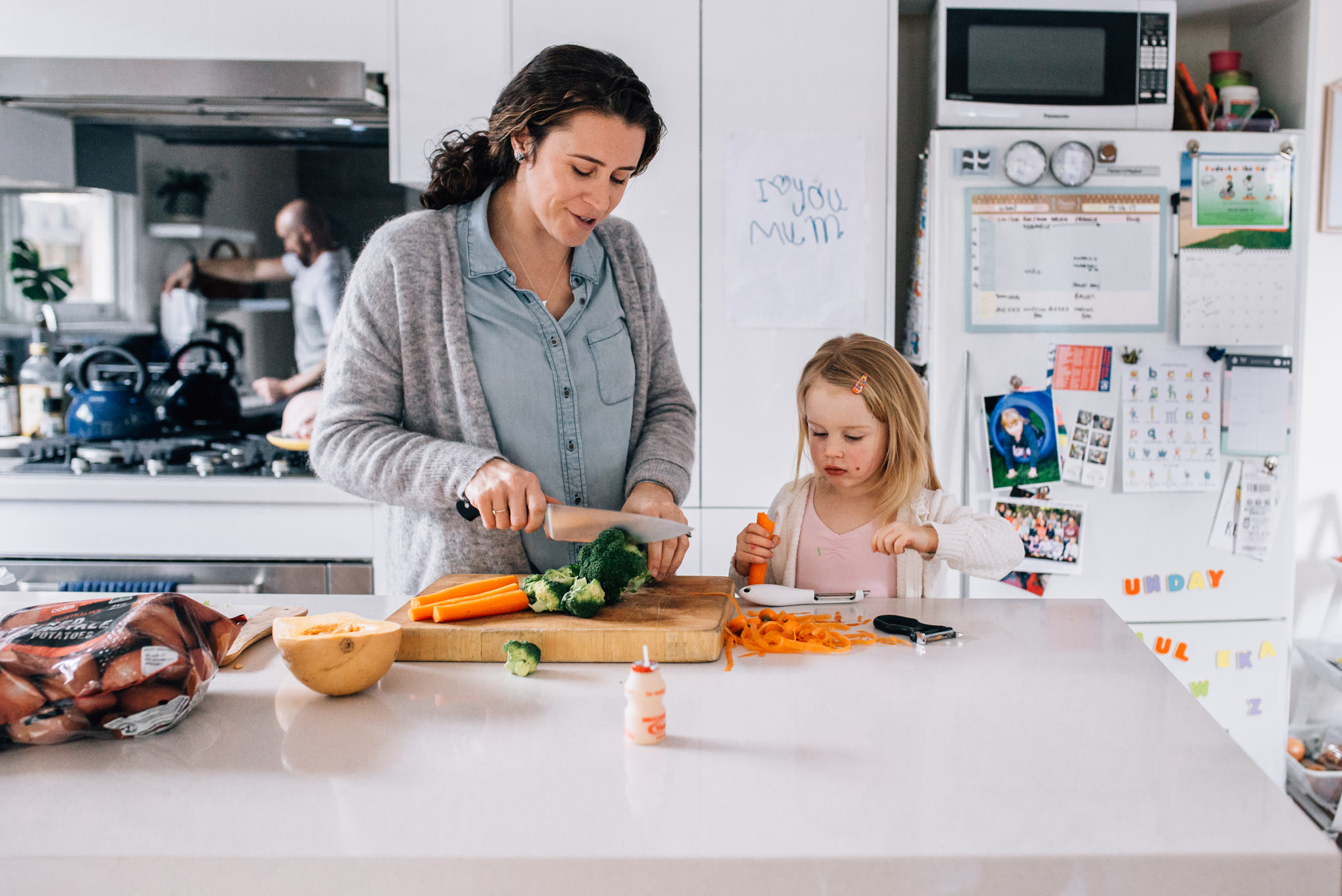 Mother and daughter chopping carrots.