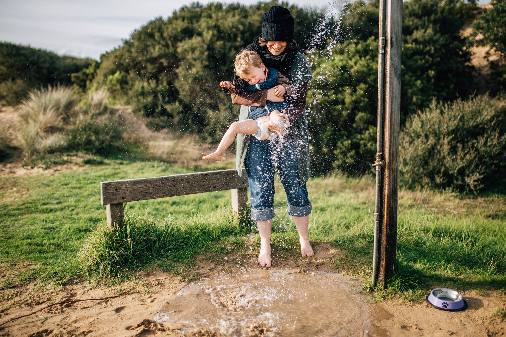 mum washing toddlers feet at beach shower (1 of 1).jpg