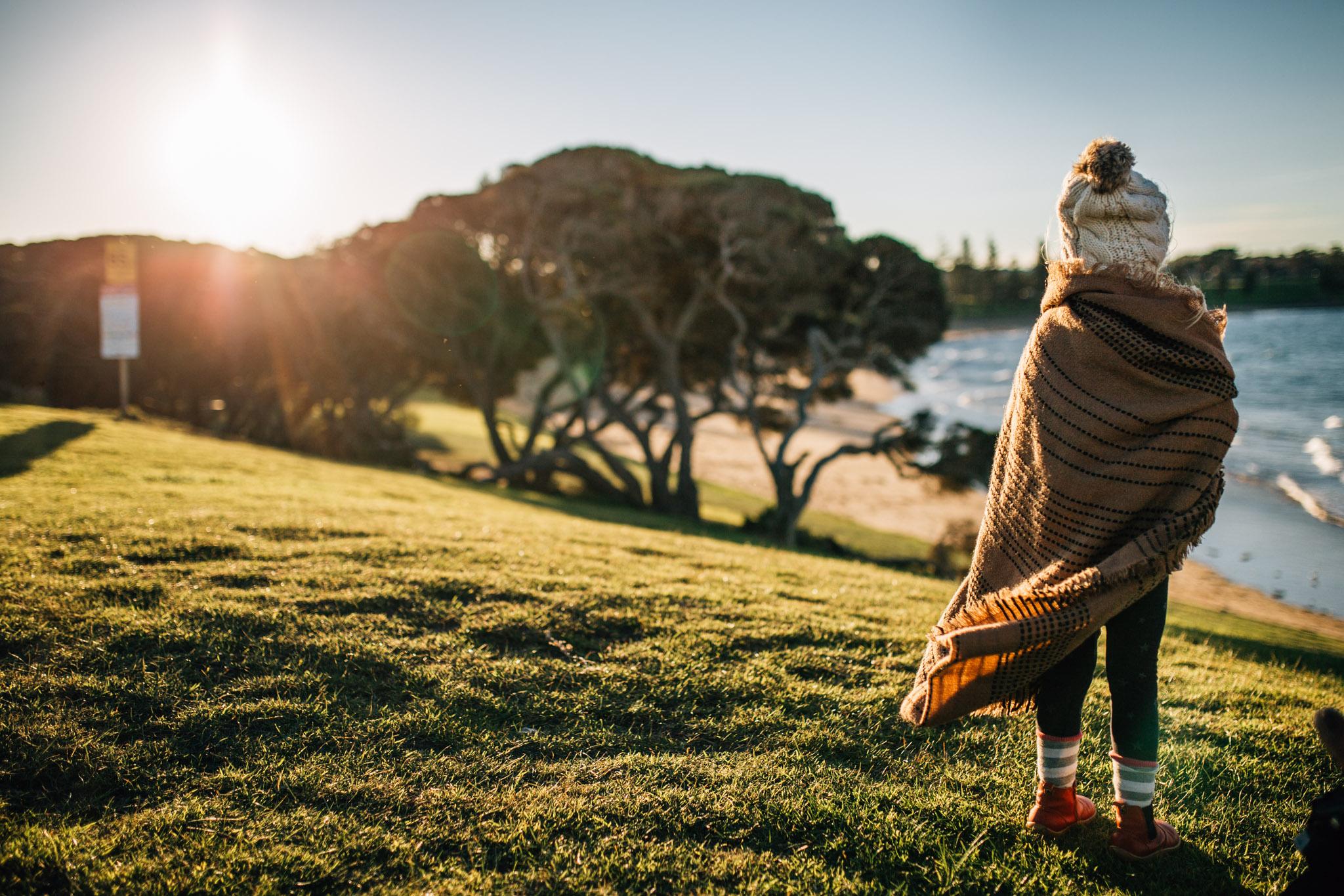 cold girl in blanket looking out over ocean (1 of 1).jpg