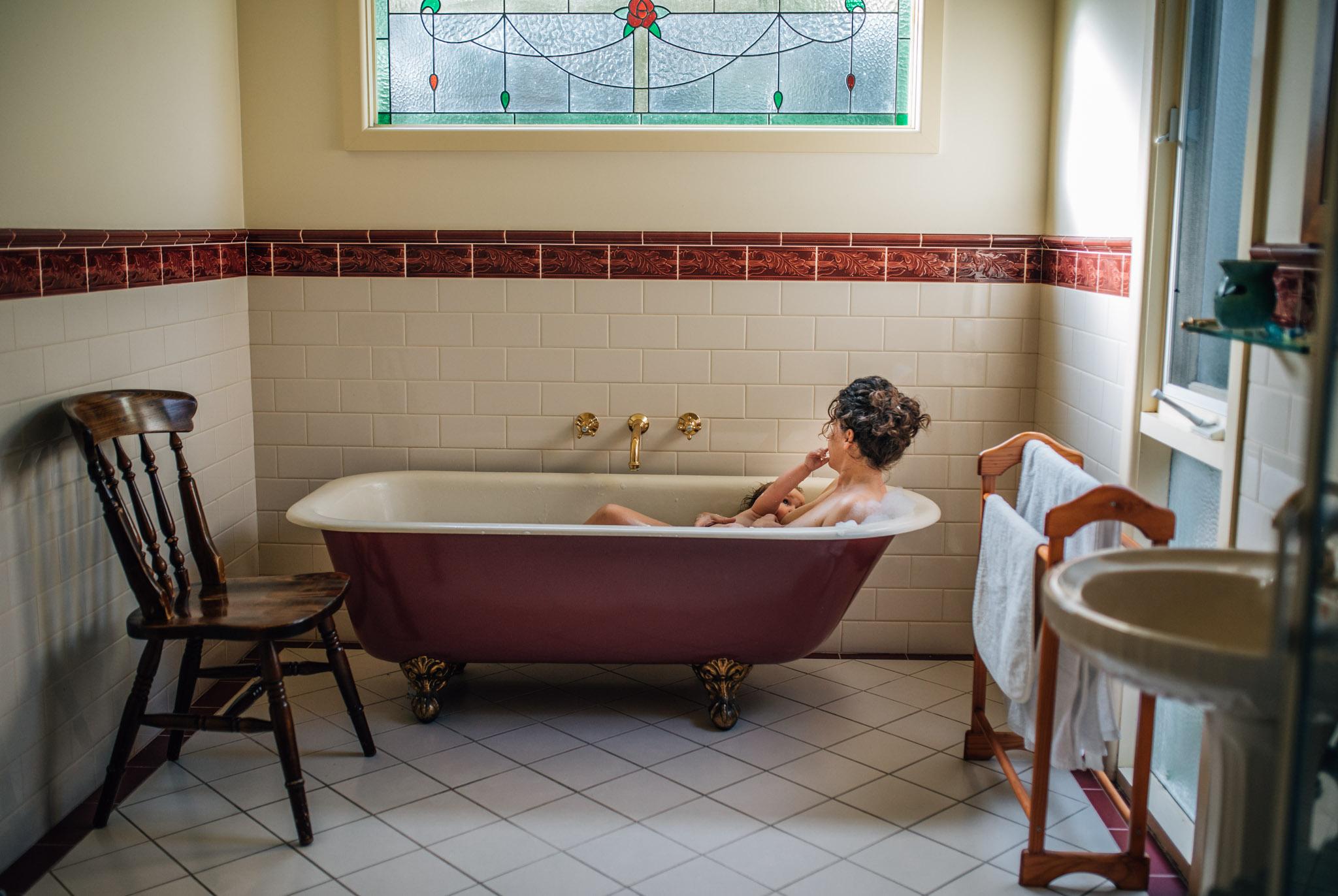 mother breastfeeding baby in clawfoot bathtub lifestyle shot III (1 of 1).jpg