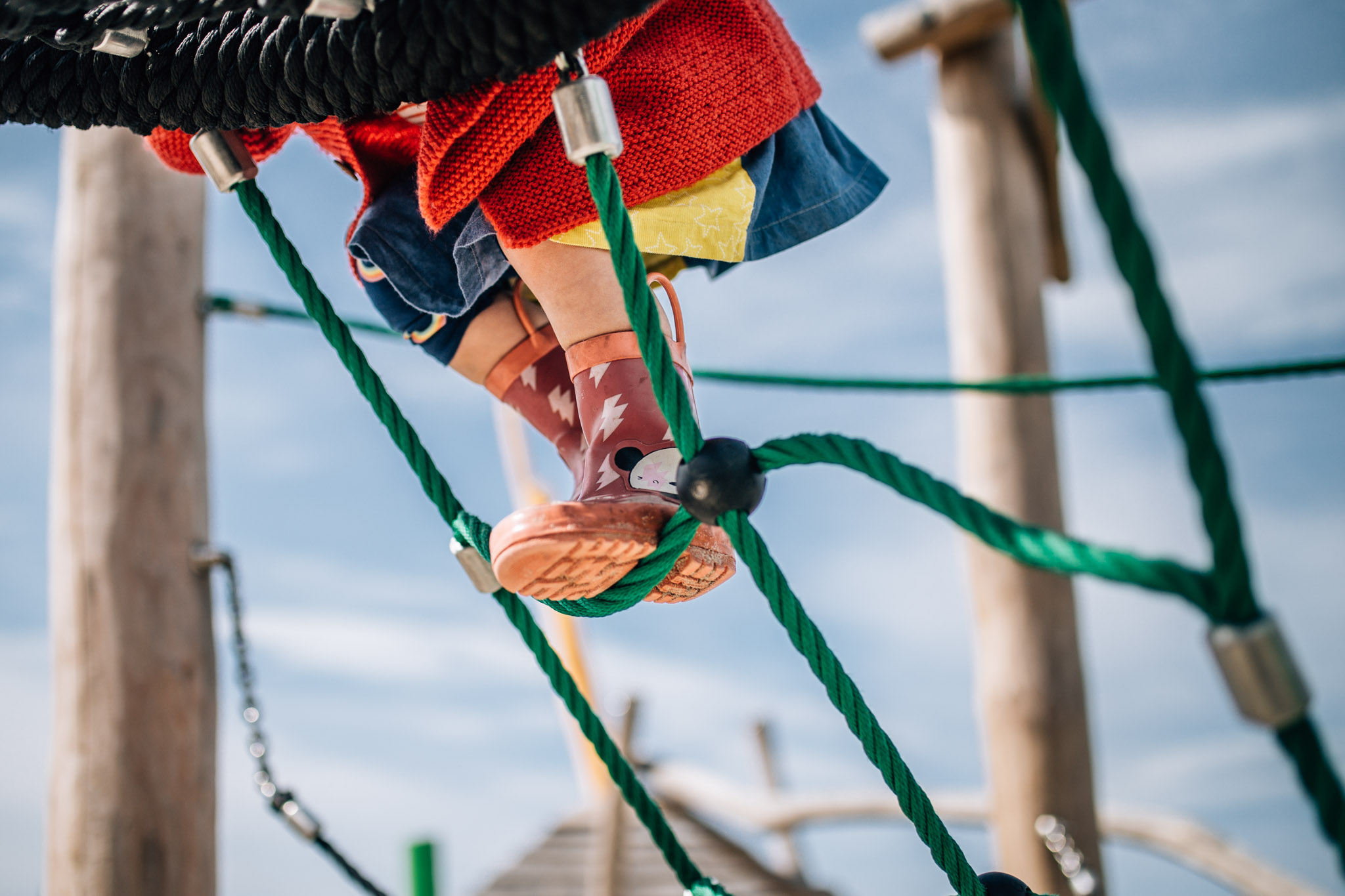 little girl in red cardigan climbing play equipment (1 of 1).jpg