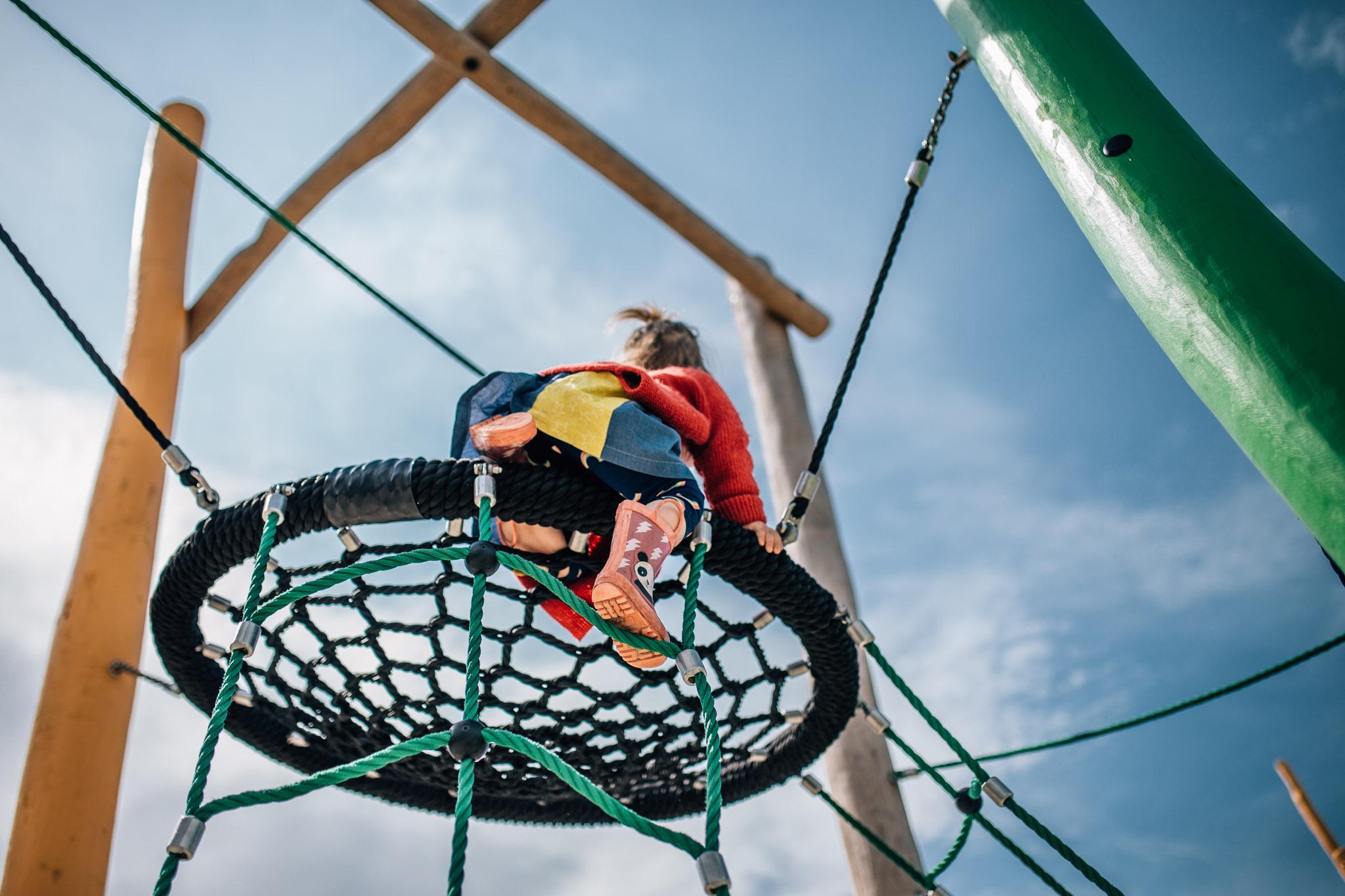little girl in red cardigan climbing play equipment III (1 of 1).jpg