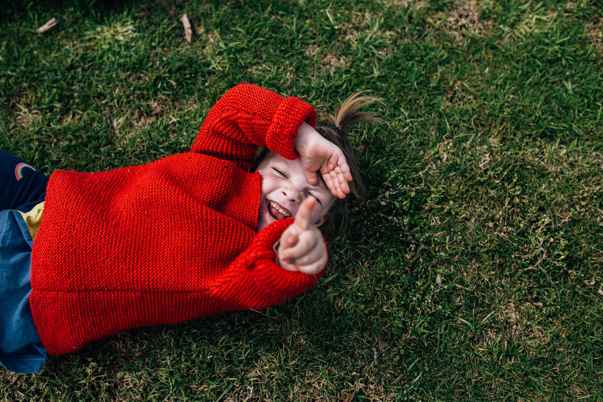 little girl in red cardigan lying in grass (1 of 1).jpg