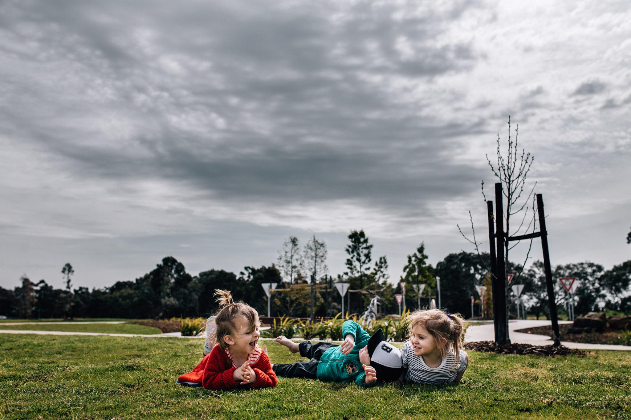 three children lying in grass (1 of 1).jpg