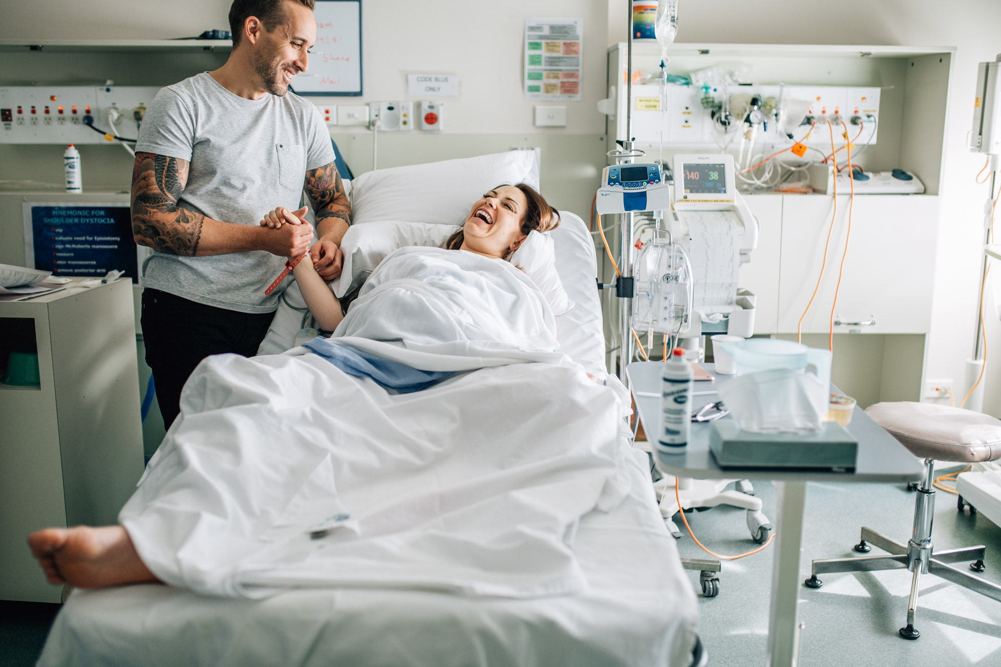 woman and man laughing over hospital bed (1 of 1).jpg