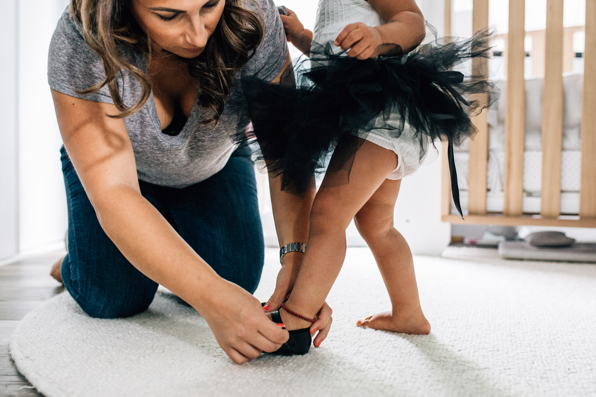 mother fixing toddler girls shoe while she wears tutu (1 of 1).jpg