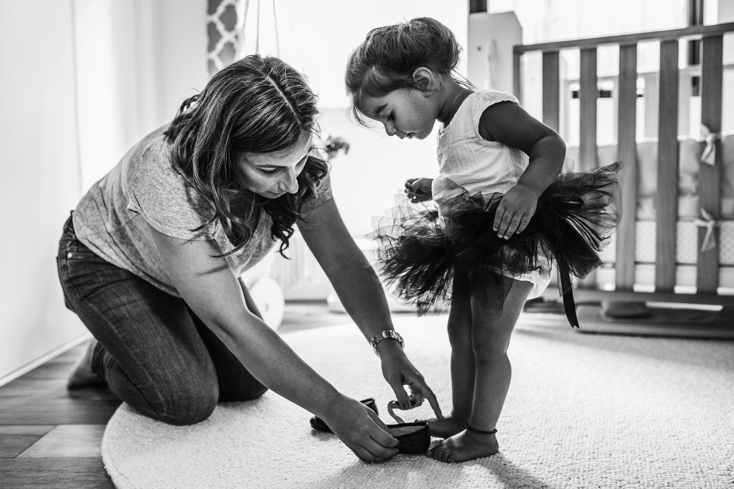 mother helping toddler girl into shoe.jpg