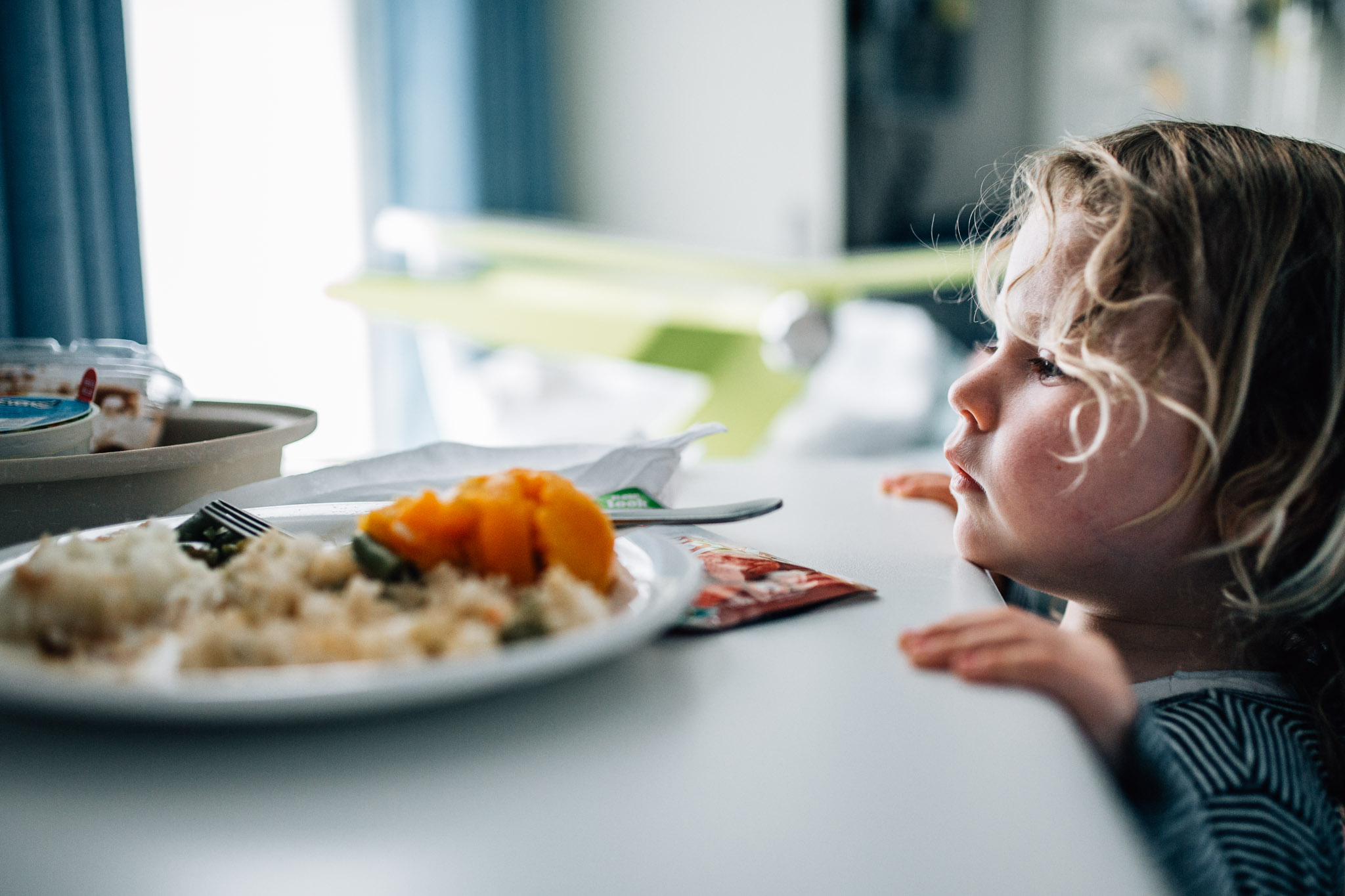 little girl staring at plate of hospital food (1 of 1).jpg
