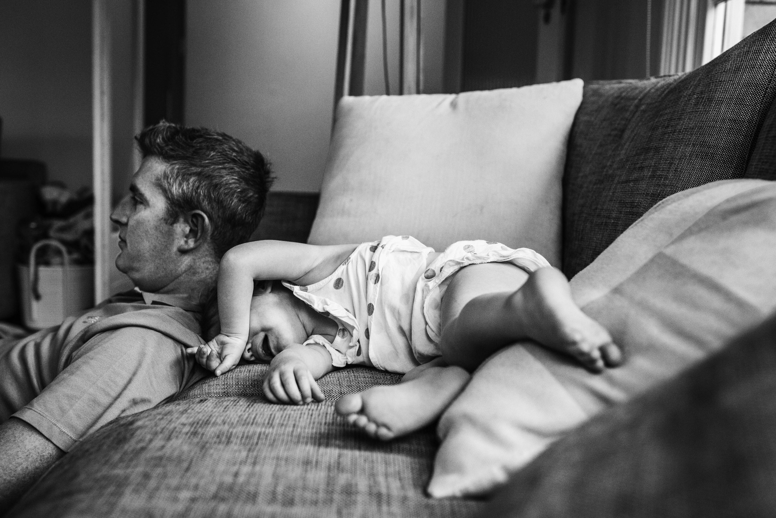 little-girl-tantruming-on-sofa-while-dad-sits-beside-her.jpg