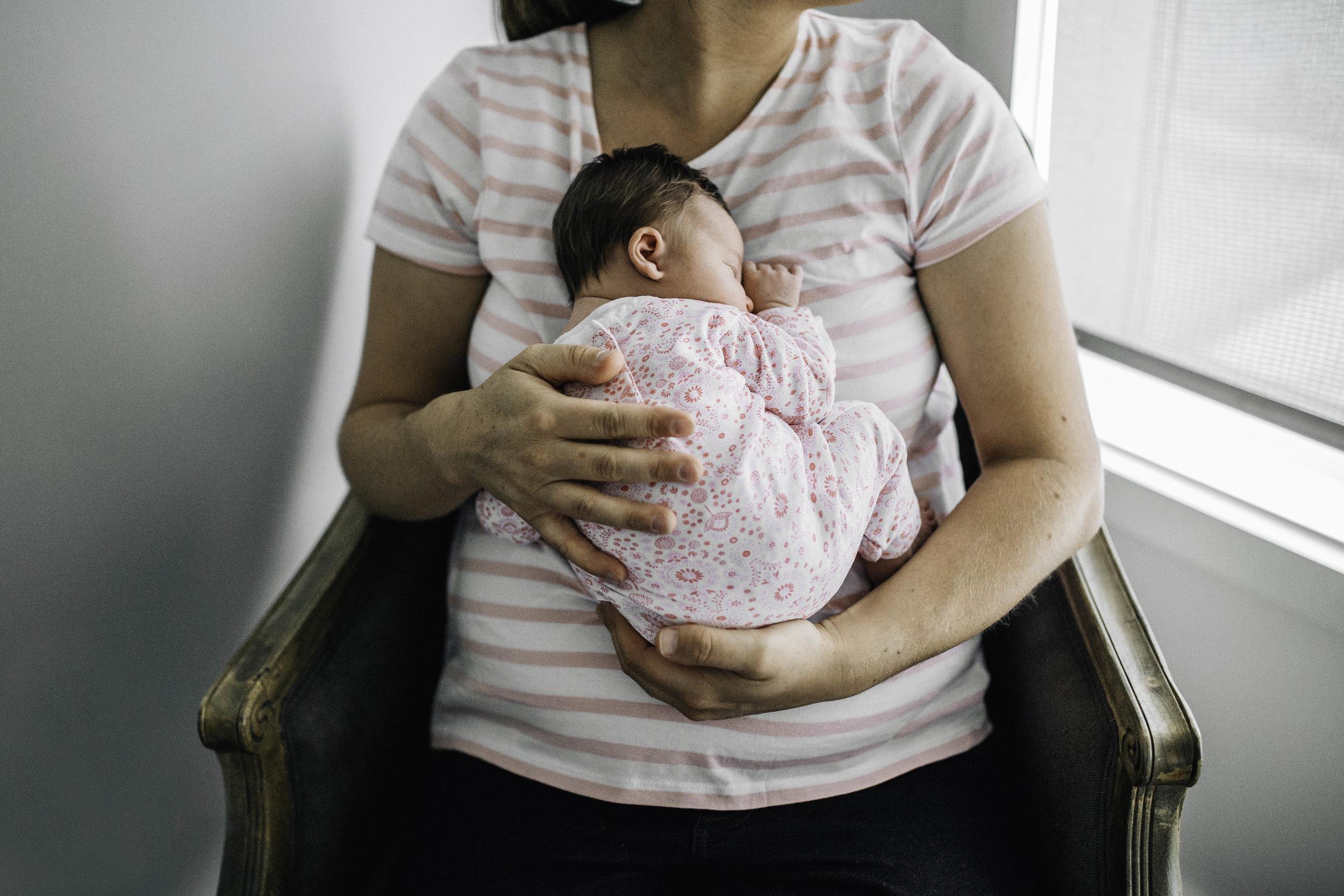 mother-cradling-newborn-baby-in-her-lap.jpg