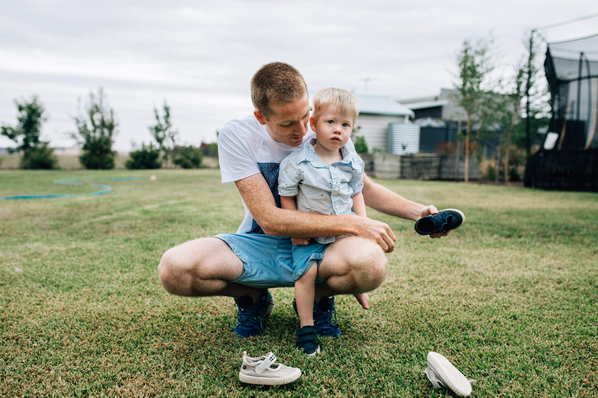 father-helping-toddler-son-with-shoes-outside (1 of 1).jpg