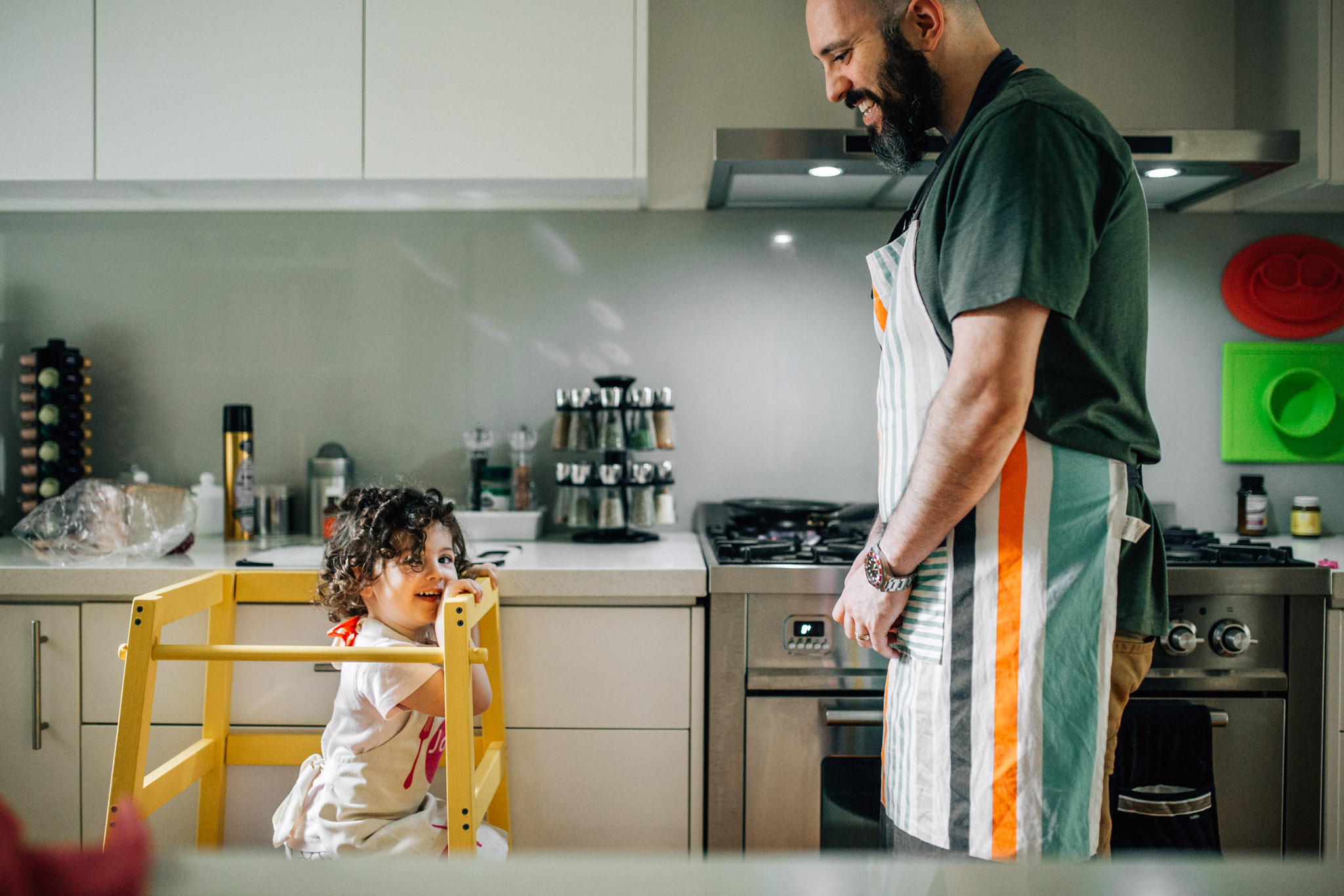 toddler-girl-squatting-on-learning-tower-in-kitchen-with-father (1 of 1).jpg