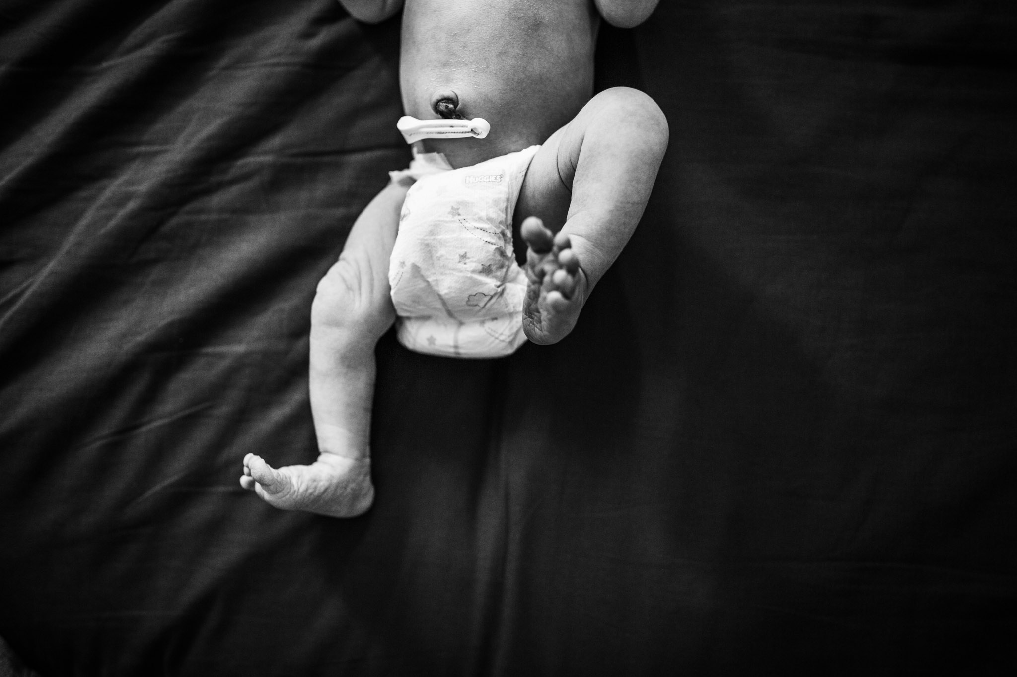 baby-kicking-legs-on-black-sheet (1 of 1).jpg
