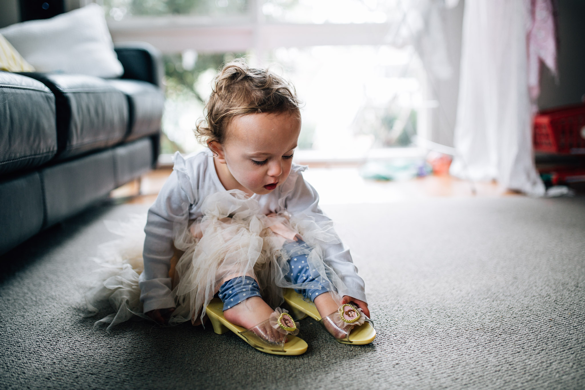 little girl putting on yellow princess slippers (1 of 1).jpg