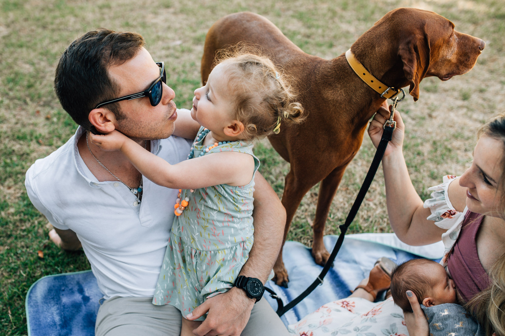 family-sitting-on-picnic-rug-daughter-and-father-kissing (1 of 1).jpg