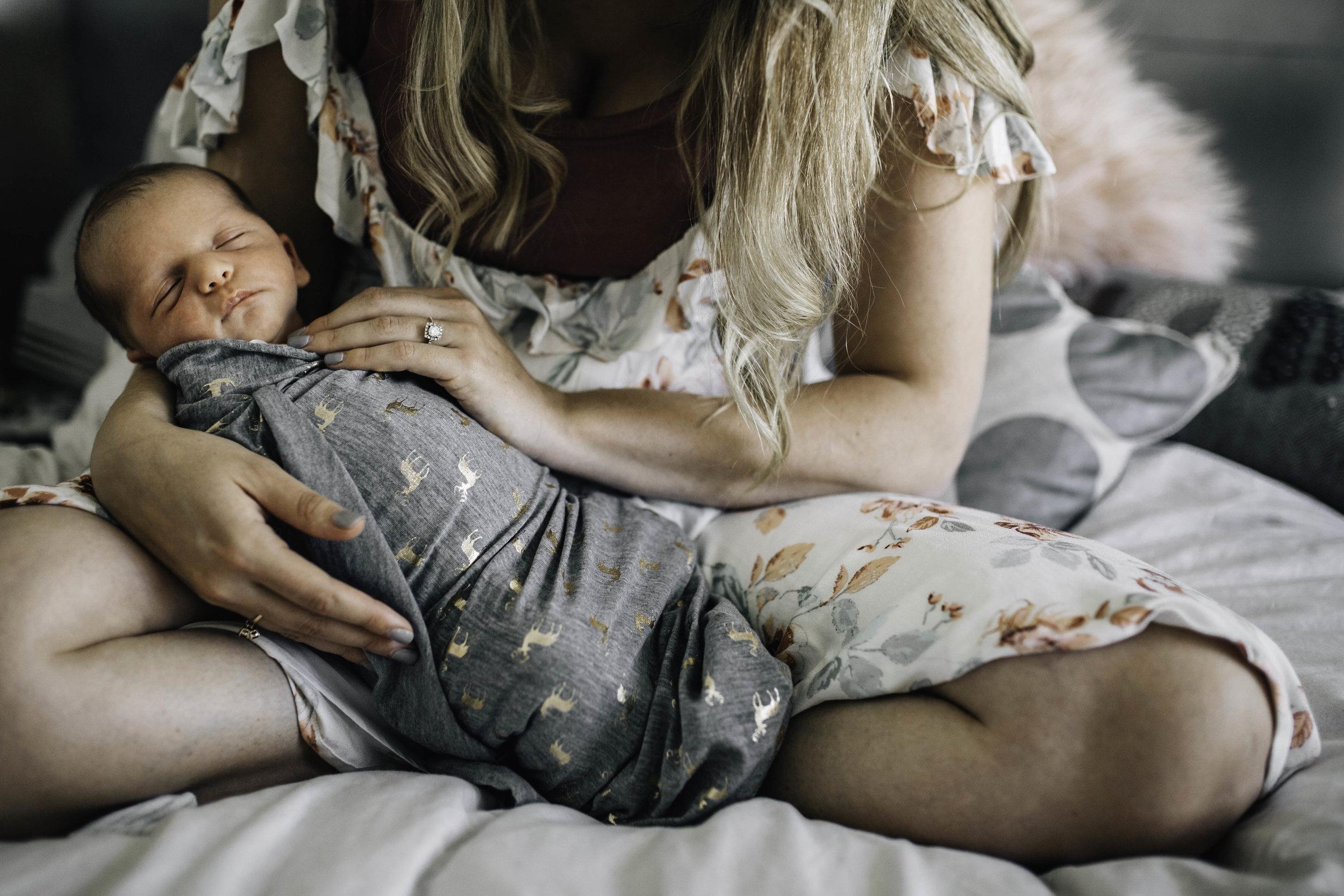 mother-cradling-newborn-son-in-her-arms.jpg