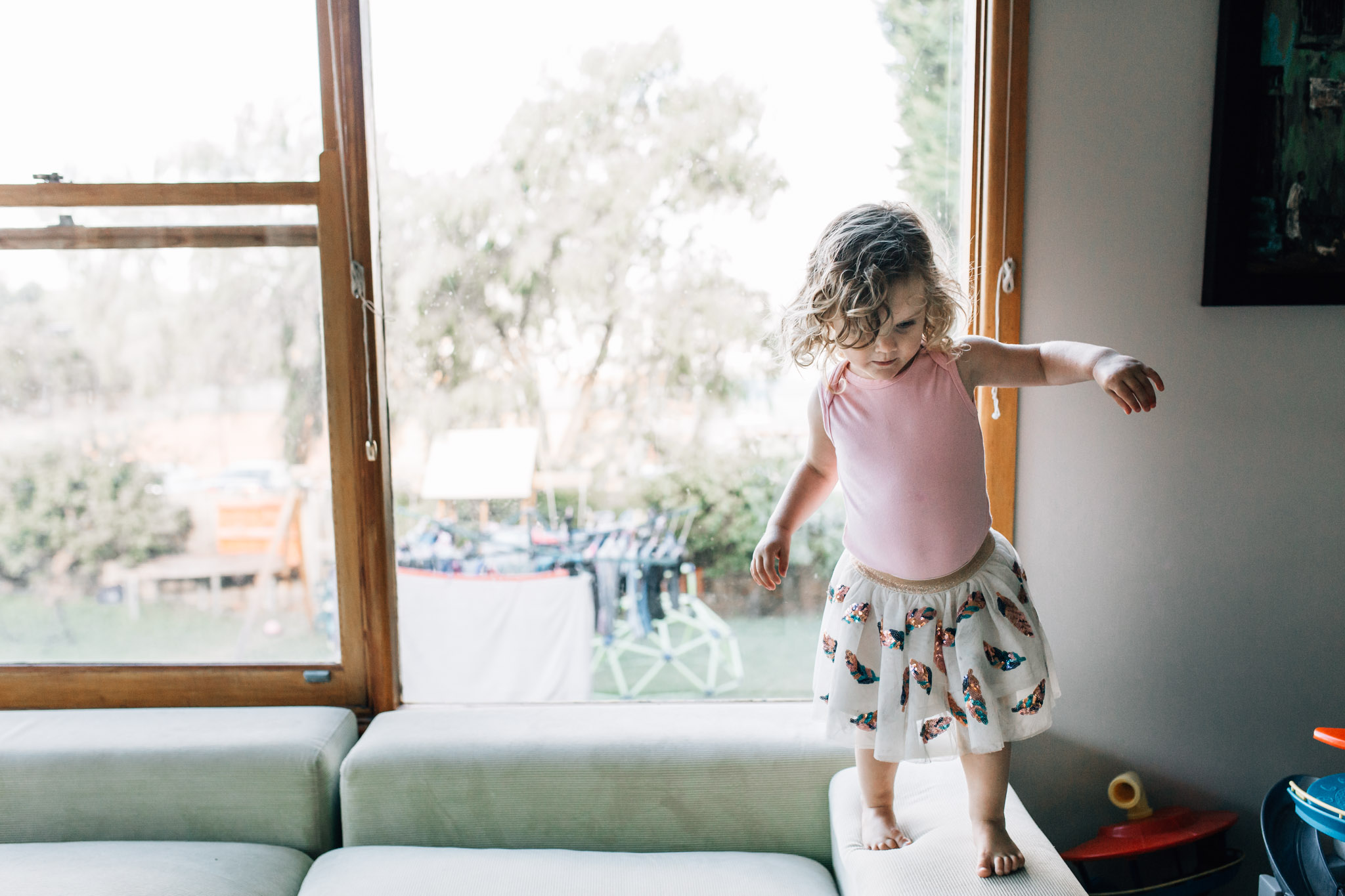 little-girl-standing-on-family-room-sofa-II (1 of 1).jpg
