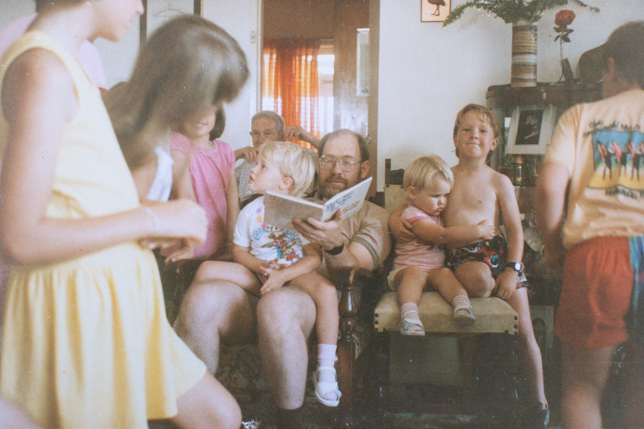 This is my uncle, reading to all the cousins after a typical family lunch. I'm the little girl in pink, my arms wrapped tightly around my older cousin.