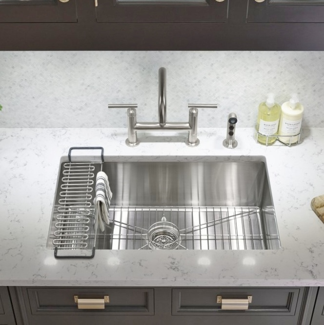 An undermount stainless steel sink with a quartz countertop.  Source -  Kohler