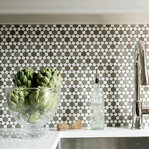 These silver and gray mosaic backsplash tiles are a great focal point. They are busy but not competing with the white counter.  Source -  DecorPad