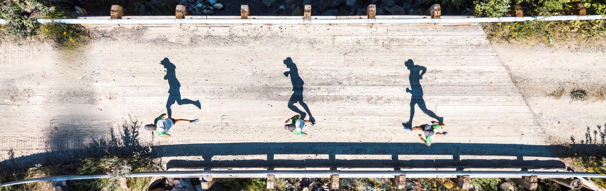 runners shadows crossing a bridge in Montana