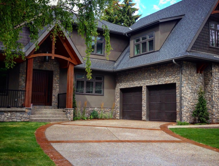 E19-luxury-home-calgary-custom-home-aggregate-driveway-curved-driveway-timber-trusses-stone-exterior-750x570.jpg