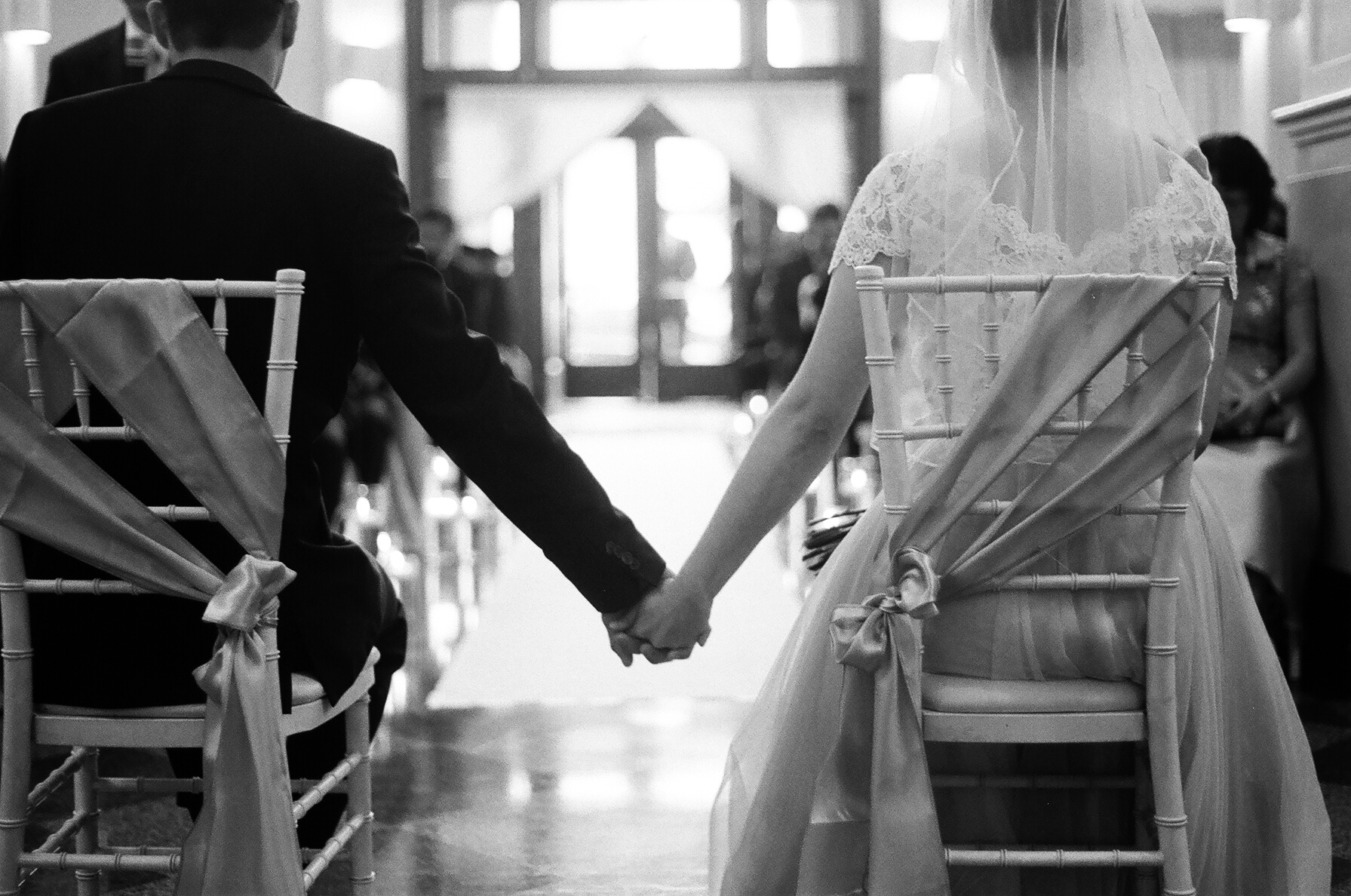 black and white photograph of bride and groom holding hands during the wedding ceremony in Everett Washington Taken by Joseph Barber photography newport beach