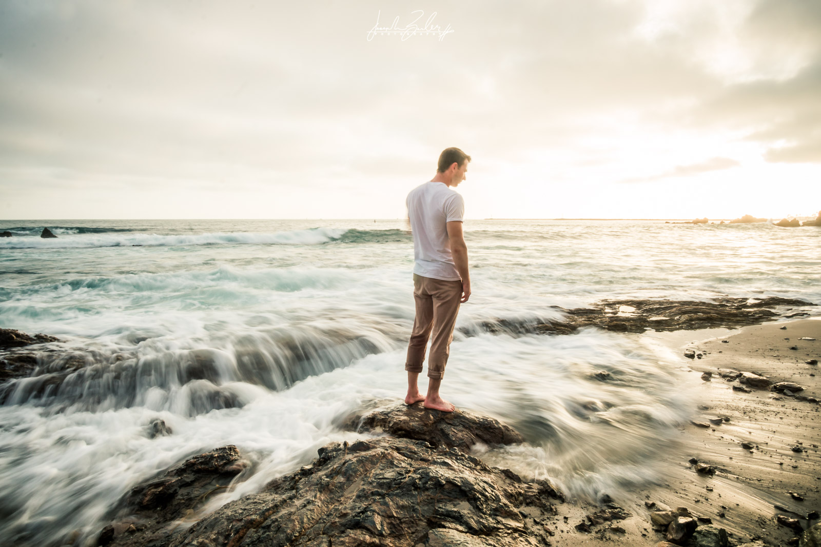 Engagement session photograph of a Fiance posing during  during Golden hour at little corona del mar beach