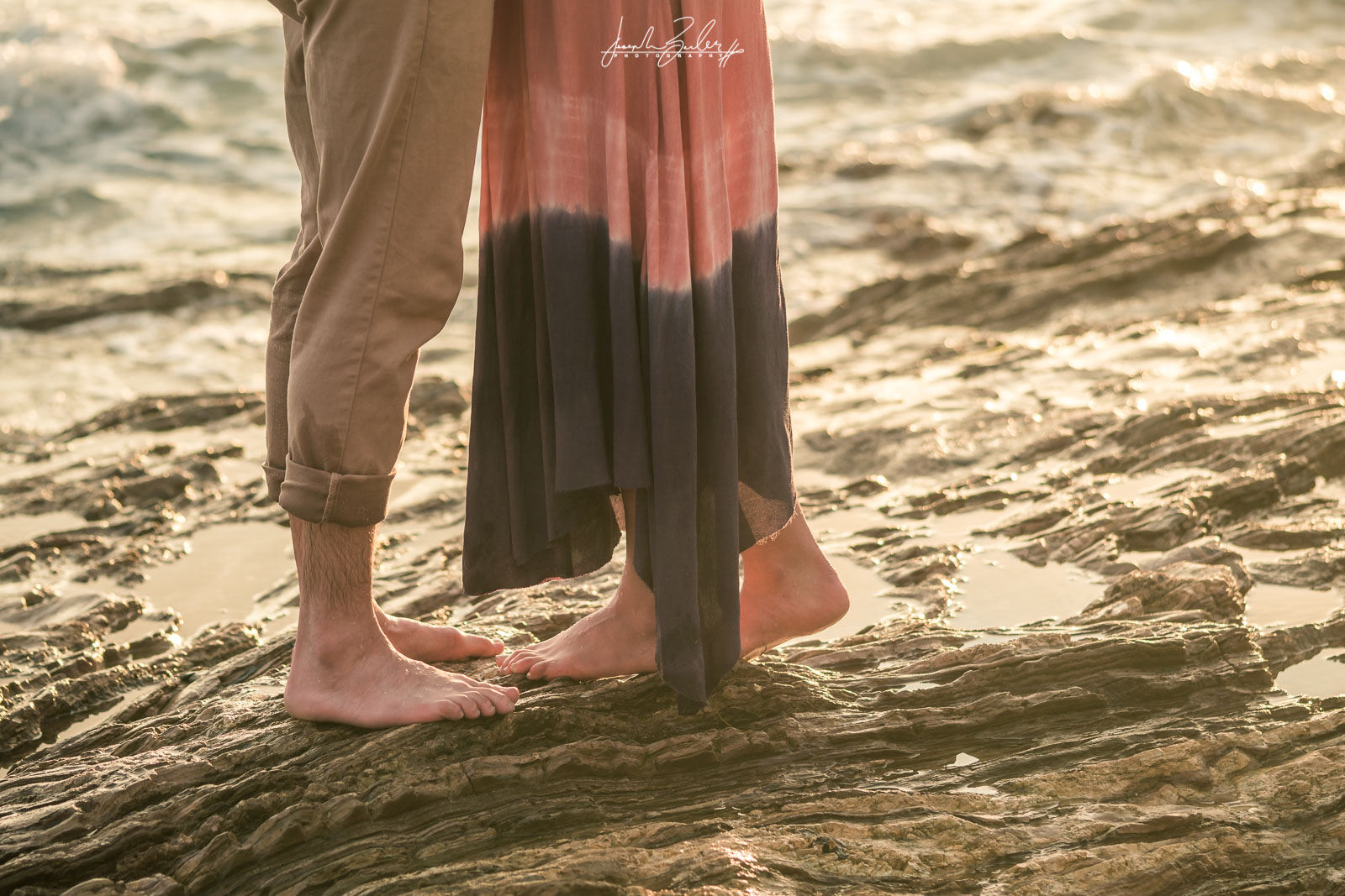 Engagement session photograph of a Couple posing Standing in the tidepools during  during Golden hour at little corona del mar beach