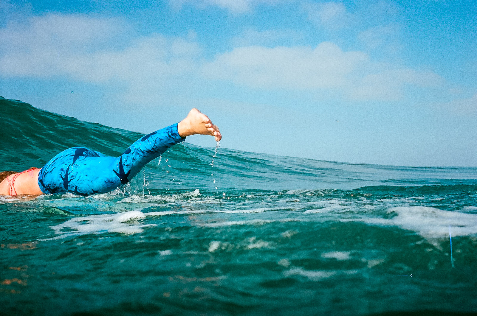 35mm color film Surfing photo shoot in the water at Huntington State Beach with girl surfer duck diving for Get wise fool eco-friendly surf company