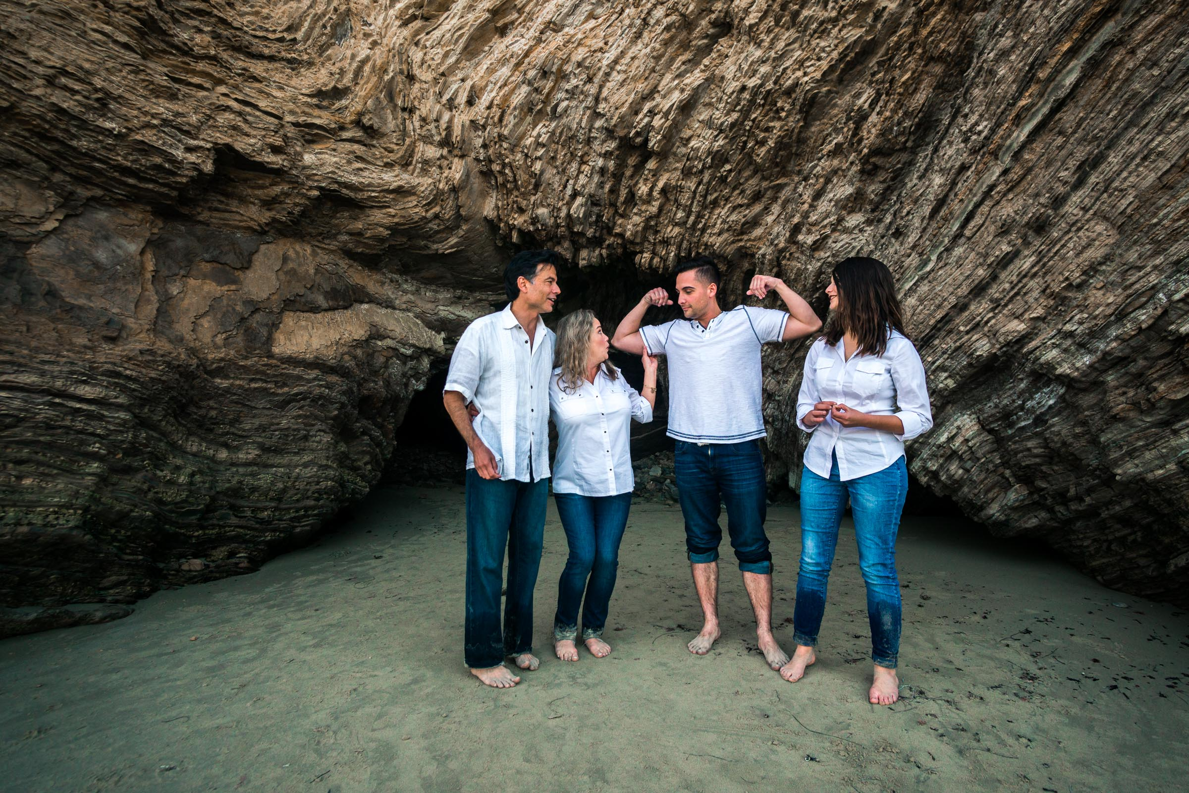 Family portraits of family posing near sea cave and cliff during Golden hour at Crystal Cove State Beach in Newport