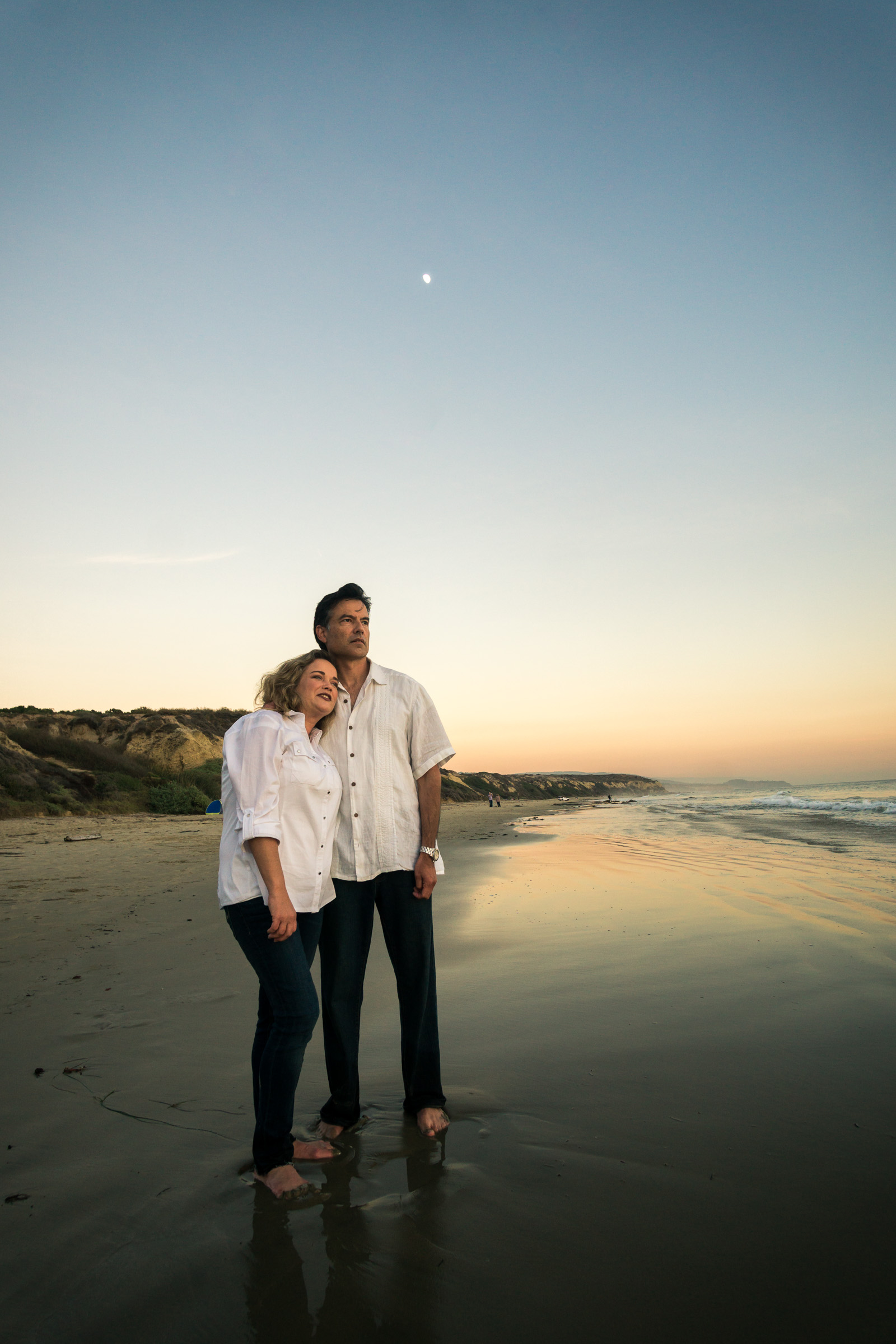 Family portraits of husband and wife with a  glassy seashore while enjoying the sunset together during Golden hour at Crystal Cove State Beach in Newport