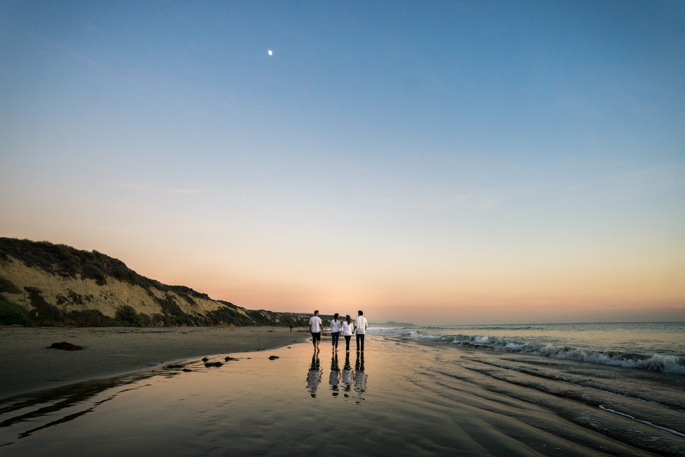 Family portraits of family walking on glassy seashore with blue sky and crescent moon while enjoying the sunset together during Golden hour at Crystal Cove State Beach in Newport