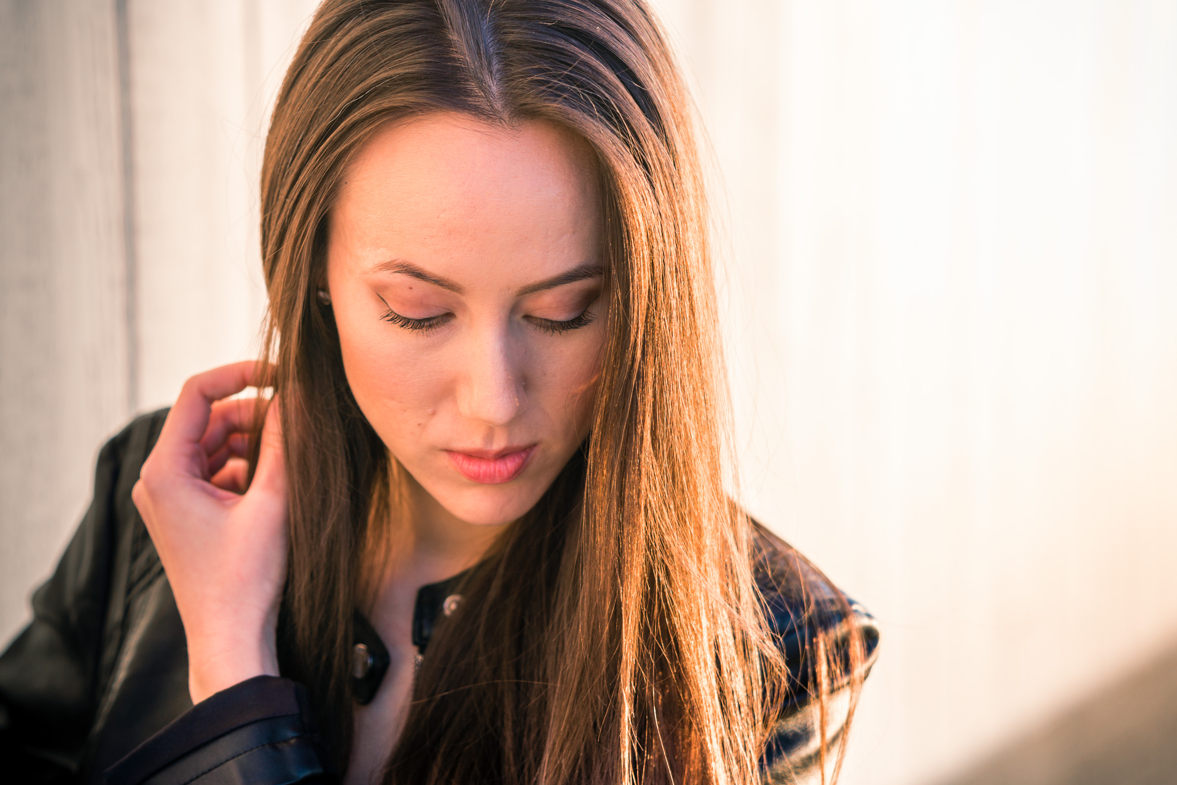 Natural light Fashion Portrait of female model wearing black leather jacket and blue jeans taken during Golden hour At Balboa Pierin Newport Beach