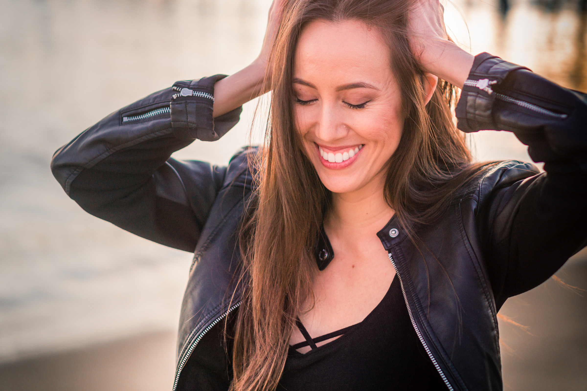 Natural light Fashion Portrait of smiling girl wearing black leather jacket and blue jeans taken during Golden hour At Balboa Pier in Orange County